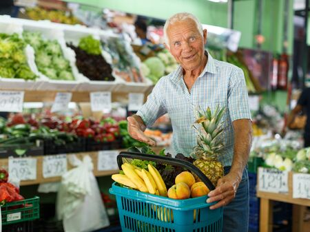 Senior man with basket with fresh greengrocery enjoying purchases in vegetable store