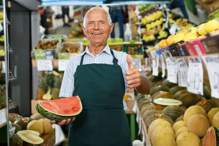 Successful senior male owner of greengrocery shop giving thumbs up, recommending fresh products