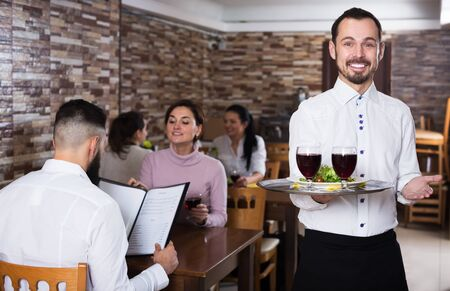Young male waiter welcoming guests to rustic restaurant Stok Fotoğraf