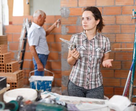 Thoughtful young woman with plastering trowel looking at repairable room Stock fotó