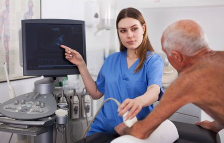 Elderly man patient undergoing examination hand by woman doctor with ultrasonography device Stock Photo