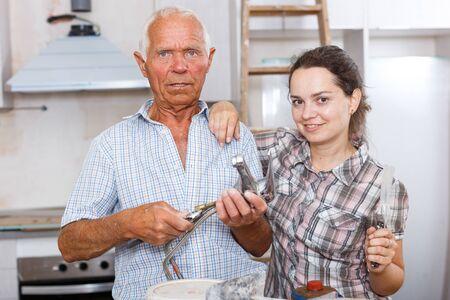Mujer joven entusiasta y su padre anciano posando juntos durante las reparaciones en su apartamento Foto de archivo