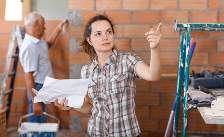 Pensive woman planning upcoming overhaul, checking with plan of house on paper