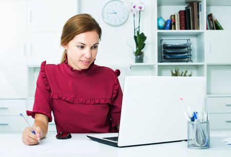 Young female employee taking notes on paper while working with laptop at office
