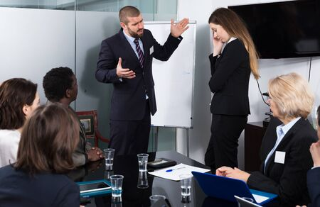 Irritated boss standing near whiteboard in meeting room, scolding subordinate woman