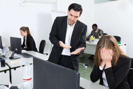 Jefe masculino enojado apuntando a faltas en el trabajo a gerente femenina que trabaja en la computadora portátil
