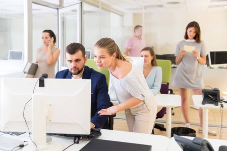 Cheerful girl helping male colleague in work with computer in modern coworking space