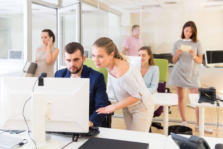 Chica alegre ayudando a un colega masculino en el trabajo con la computadora en el espacio de coworking moderno