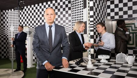 Confident businessman standing in stylized quest room on background with colleagues solving conundrums Stock Photo