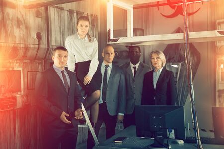 Portrait of group of thoughtful people in business suits at escape room Stock Photo