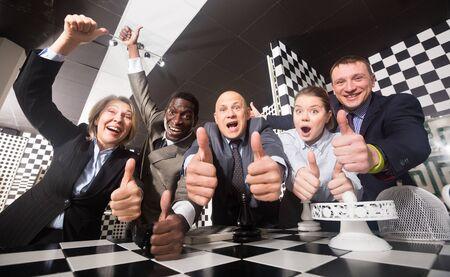 Glückliche Geschäftsleute posieren emotional im Schwarz-Weiß-Questraum. Erfolgreiches Teamwork-Konzept