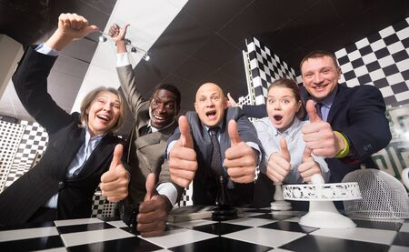 Happy businesspeople emotionally posing in black and white quest room. Successful teamwork concept