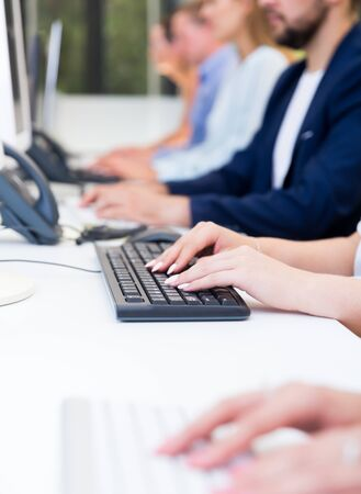 Focus on female hands typing on keyboard during daily work in coworking space