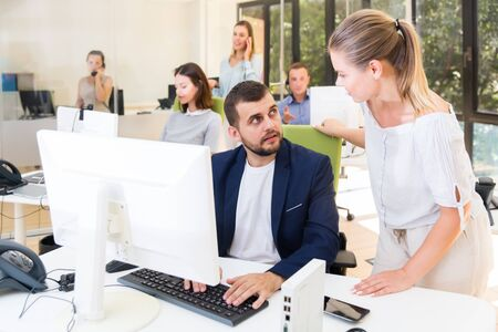 Fine girl helping male colleague in work with computer in modern coworking space Stockfoto - 131827712