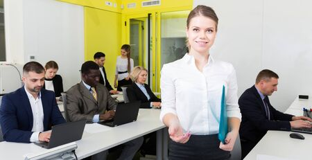 Elegant young businesswoman holding clipboard welcoming to busy modern coworking space