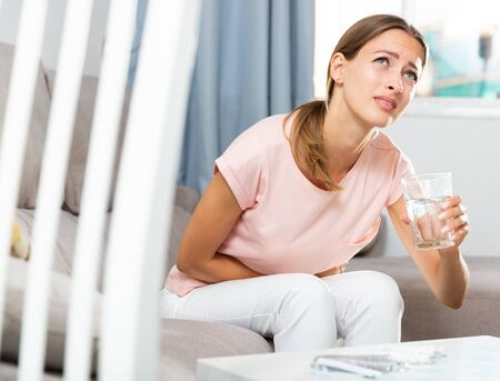 Unhappy female having stomachache sitting on sofa at home Stock Photo