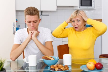 Senior mother lecturing her sad adult son at kitchen