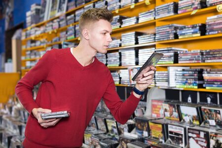 Focused man choosing for interesting movies on shelves of CD shop