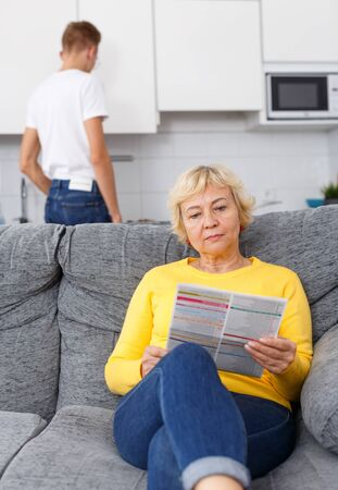 Senior woman reading booklet on sofa while her adult son cooking breakfast