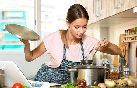 Positive young housewife cooking vegetable soup and using laptop at kitchen