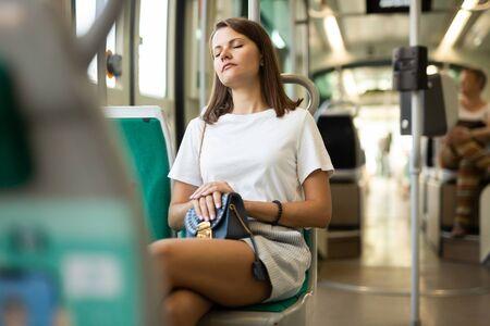 Porträt einer jungen Frau, die am frühen Morgen mit geschlossenen Augen mit dem Bus oder der Straßenbahn zur Arbeit geht Standard-Bild