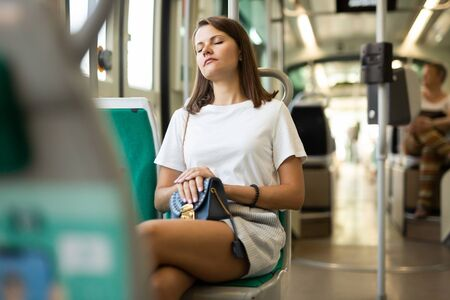 Portrait of young woman going to work by bus or trolley at early morning sitting with closed eyes