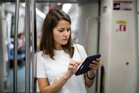 Portrait of young smiling woman using tablet standing in subway car leaning on handrail