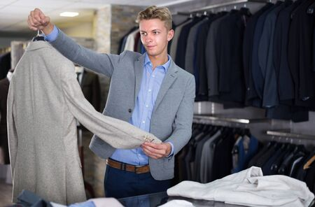 Man customer in business suit choosing colored jacket in the dress shop