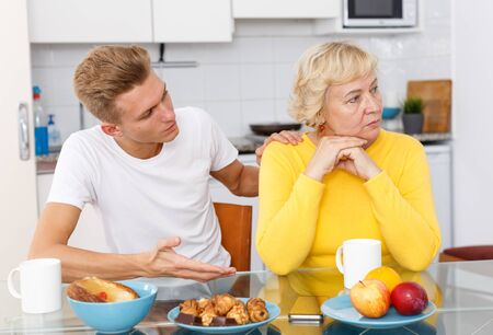 Young guy asking for forgiveness his offended mother at kitchen