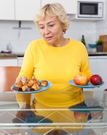 Portrait of friendly mature woman choosing healthy lifestyle and eating fruits at kitchen
