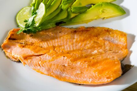 Photography of plate with fried trout fillet with avocado in restaurante. Imagens
