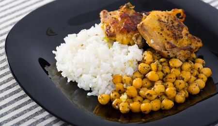 Tasty chicken thighs with garbanzo and rice at plate on table Imagens