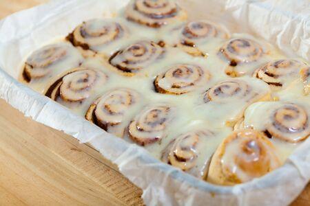 Freshly baked homemade cinnabons cinnamon rolls with milk sugar icing in baking dish