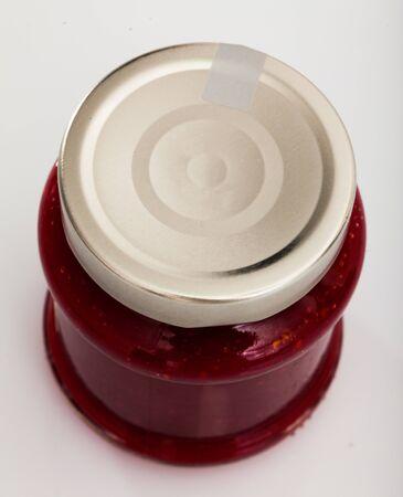 Barattolo di vetro chiuso di deliziosa marmellata di lamponi fatta in casa su sfondo bianco Archivio Fotografico