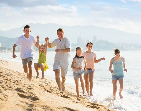 Large happy family of six people running together on beach on summer day