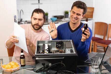 Two men repairing a desktop computer and drink beer Stock Photo