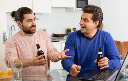 Smiling men sitting at table and drinking beer indoor Фото со стока