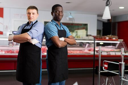 Two confident professional butchers standing in hall of butcher shop
