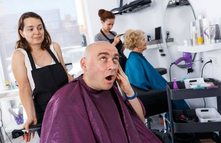 Bald man unpleasantly surprised by haircut from young woman hairdresser expressing regret in salon