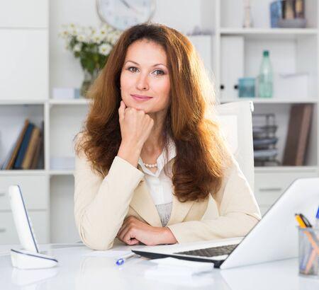 Portret van een vrouw die met documenten en laptop op kantoor werkt. Stockfoto