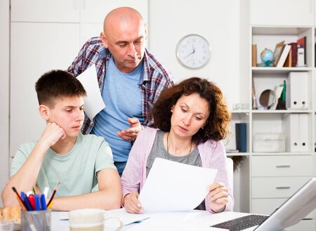 Young woman with her husband and teen son calculating domestic budget at table