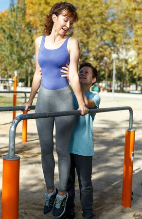 Smiling sportive woman and teenage boy exercising together on parallel bars on sports ground at sunny autumn day Фото со стока