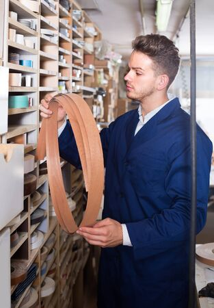 Young smiling guy choosing strips to end edgings at workshop