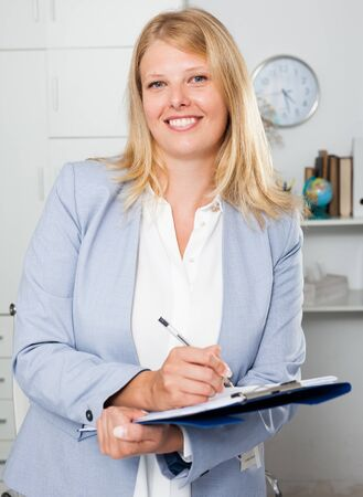 Portrait of adult confident businesswoman with folder standing in office interior