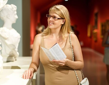 Woman with spectacles holding information brochure in her hands and looking at exposition in museum of arts Foto de archivo