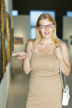 Woman wearing glasses throwing up her hands near the picture in art museum hall