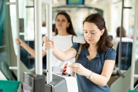 Young woman inserting ticket in modern punching machine, validating ticket in public transport