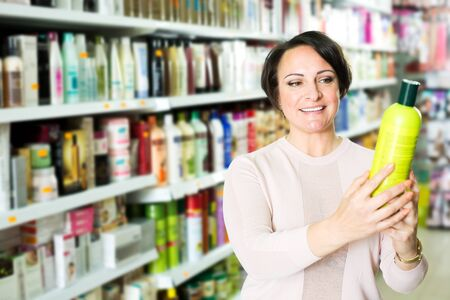 Pretty female customer buying conditioner for hair in supermarket