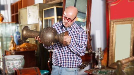 focused man visiting shop of antique goods in search of interesting objects