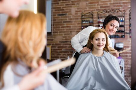 Adult hairdresser is listening to wishes of young woman about her hairstyle.